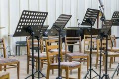Lege zetels en sommige instrumenten in muziekzaal die op orkest wachten om op het stadium te komen zwarte muziektribune op stadiu stock foto
