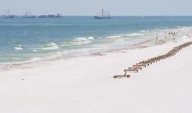 Lege zitkamerstoelen op met olie doordrenkt strand Stock Fotografie