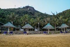 Lege zonlanterfanters en bamboeparasol op het tropische overzees stock foto