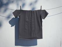 Lege zwarte t-shirt op een kabel dichtbij muur het 3d teruggeven Royalty-vrije Stock Afbeelding