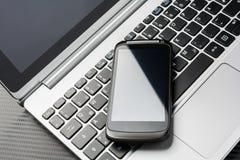 Lege Zwarte Zaken Smartphone met Bezinning die op een Notitieboekjetoetsenbord liggen, allen boven een Koolstoflaag Royalty-vrije Stock Foto