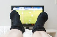 Legen in Bett und in überwachenden Fernsehapparat stockfoto