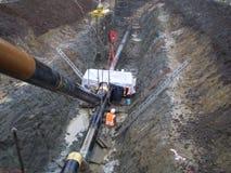 Legen der Erdgasleitung in einem Abzugsgraben Installationsarbeiten Stockbilder