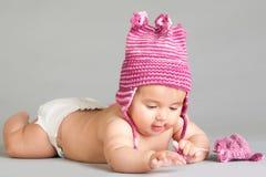 Legen des Schätzchens in der stripy rosafarbenen Schutzkappe stockbilder
