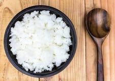Legen Sie Reis in eine Schale auf einen Holztisch Stockbild