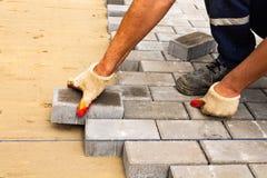 Legen von grauen konkreten Pflastersteinen im Haushof-Fahrstraßenpatio Berufsarbeitskraftmaurer installieren neue Fliesen oder lizenzfreie stockbilder