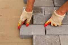 Legen von grauen konkreten Pflastersteinen im Haushof-Fahrstraßenpatio Berufsarbeitskraftmaurer installieren neue Fliesen oder stockfotos