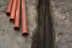 Legen von Kabeln und von Rohren im Graben Stockfotografie