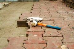 Legen von Pflastersteinen durch Mosaiknahaufnahme Pflasternde Straße, Bau Arbeitskräfte, die Pflasterstein des Steins legen Legen Lizenzfreies Stockbild