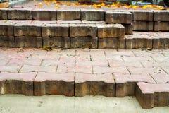 Legen von Pflastersteinen durch Mosaiknahaufnahme Pflasternde Straße, Bau Arbeitskräfte, die Pflasterstein des Steins legen Legen Stockfotografie