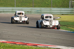 Legend Supercar Racing. ASSEN, NETHERLANDS - OCTOBER 19, 2014: Two Legend supercars racing through a chicane on the TT Assen circuit Royalty Free Stock Image
