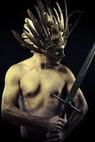 Legend, Warrior with helmet and sword with his body painted gold Stock Image