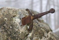 Legendariskt Excalibur svärd in i stenen i mitt av foen arkivfoton