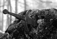 Legendariskt Excalibur svärd in i stenen i mitt av foen arkivbild