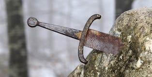 Legendariskt Excalibur svärd in i stenen i mitt av foen arkivbilder
