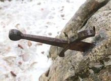 Legendariskt Excalibur svärd in i stenen i mitt av foen royaltyfria bilder