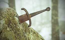 Legendariskt Excalibur svärd in i stenen i mitt av foen royaltyfri fotografi