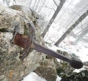 Legendariskt Excalibur svärd in i stenen i mitt av foen royaltyfri bild