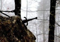 Legendariskt Excalibur svärd in i stenen i mitt av foen arkivfoto