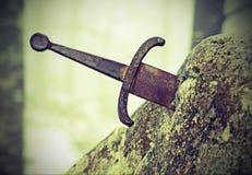 Legendariskt Excalibur svärd in i stenen med tappningeffekt fotografering för bildbyråer