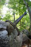 Legendariskt och berömt svärd Excalibur som gör till kung fastnat mellan ret royaltyfri bild