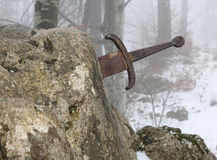 Legendary Excalibur sword into the stone in the middle of the fo. Rest in winter Stock Photo