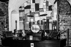 Legendary stage where The Beatles were playing. The Beatles music instruments on the legendary stage at The Cavern Club in Liverpool. Guitars, drums, piano, mic Stock Image