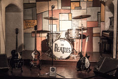 Legendary stage where The Beatles were playing. The Beatles music instruments on the legendary stage at The Cavern Club in Liverpool. Guitars, drums, piano, mic Stock Photo
