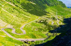 Legendary Tranfagarasan road in Romanian mountains. Legendary Transfagarasan road in Romanian mountains. winding serpentine among the grassy hills on a sunny royalty free stock image