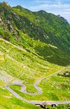 Legendary Tranfagarasan road in Romanian mountains. Legendary Transfagarasan road in Romanian mountains. winding serpentine among the grassy hills on a sunny Stock Photo