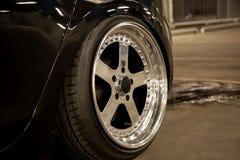 Legering opgepoetste randen van een sportwagen Brede wielen met uitgerekte banden Gestemde lage auto royalty-vrije stock afbeeldingen