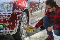 Legeringen för ` s för bilen för manarbetartvagningen rullar på en biltvätt royaltyfria foton