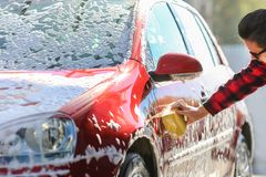 Legeringen för ` s för bilen för manarbetartvagningen rullar på en biltvätt royaltyfri foto