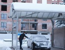 Legeringen för ` s för bilen för manarbetartvagningen rullar på en biltvätt Begrepp av biltvätt royaltyfria foton