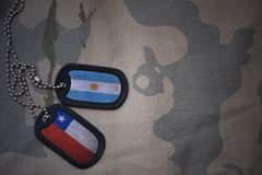 legerspatie, hondmarkering met vlag van Argentinië en Chili op de kaki textuurachtergrond Stock Fotografie