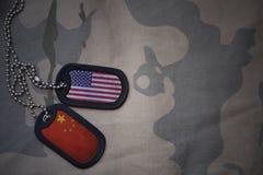 legerspatie, hondmarkering met vlag van de Verenigde Staten van Amerika en China op de kaki textuurachtergrond Stock Foto