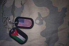 legerspatie, hondmarkering met vlag van de Verenigde Staten van Amerika en Jordanië op de kaki textuurachtergrond stock foto's