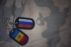 legerspatie, hondmarkering met vlag van Rusland en moldova op de kaki textuurachtergrond stock foto's