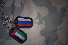 legerspatie, hondmarkering met vlag van Rusland en verenigde Arabische emiraten op de kaki textuurachtergrond royalty-vrije stock foto's