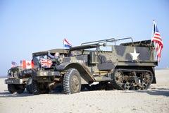 Legervrachtwagens van de Helden die van de organisatiehoed op strand berijden Stock Foto