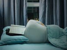Legga il libro e cada come addormentato a letto Immagini Stock Libere da Diritti