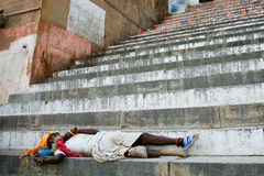 Legged sadhu sleeping on the stairs of a ghat, India stock photo