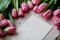 Leggen de willekeurig verspreide roze tulpen op een houten textuur, Kraftpapier-envelop Royalty-vrije Stock Foto