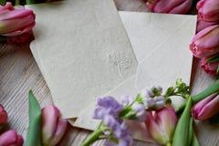 Leggen de willekeurig verspreide roze tulpen op een houten textuur, Kraftpapier-envelop Royalty-vrije Stock Afbeelding