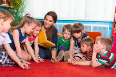 Leggendo ai bambini all'asilo Fotografie Stock Libere da Diritti