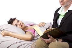 Leggendo alla figlia malata Immagine Stock