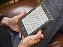Leggendo con un E-lettore di accensione Fotografie Stock Libere da Diritti