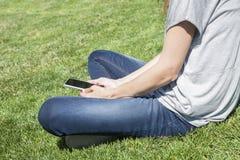 Leggendo il telefono di schermo in bianco fornito di gambe sull'erba Immagini Stock Libere da Diritti