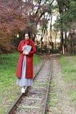 Leggendo in natura è il mio hobby, la ragazza fa il libro e la passeggiata in mezzo alla ferrovia Immagine Stock