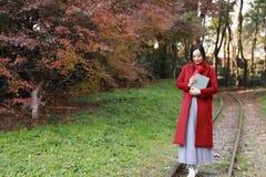 Leggendo in natura è il mio hobby, la ragazza fa il libro e la passeggiata in mezzo alla ferrovia Fotografie Stock